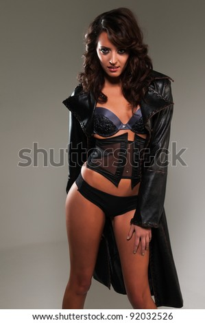 Beautiful young brunette in lingerie and trenchcoat