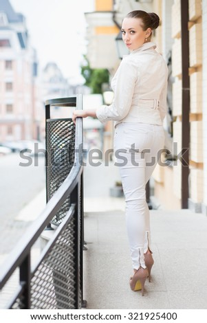Beautiful young brunette in white pants and jacket posing outdoors - stock photo