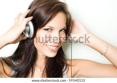 Beautiful young brunette listening to music in silver headphones.