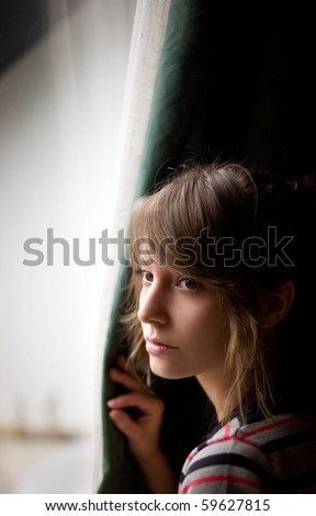 Beautiful young brunette looking out the window. - stock photo