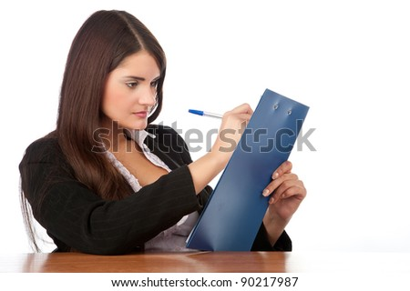 beautiful young brunette pin-up girl sitting at a desk with tablet in hand, isolated over white