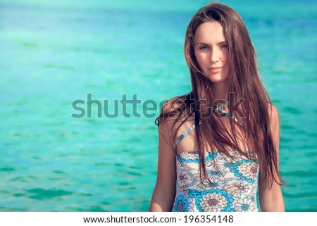 Beautiful young brunette resting at beach in summer - stock photo