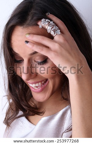 beautiful young brunette smiling girl showing lot of engagement rings and overjoyed by beautiful ring made of white gold with diamonds - stock photo