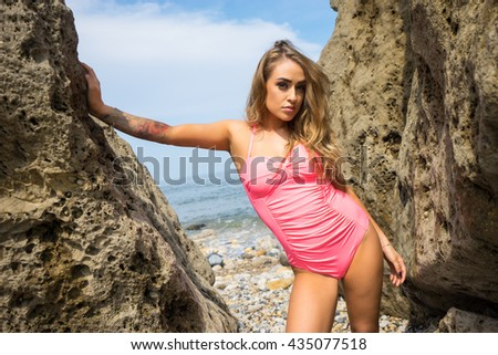 Beautiful young brunette, stood between the rocks, the sea behind her.  She has green eyes, tanned skin, is wearing a pink bathing suit, and has her left forearm tattooed. - stock photo