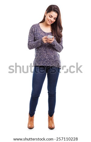 Beautiful young brunette using her smartphone to do some social networking on a white background - stock photo