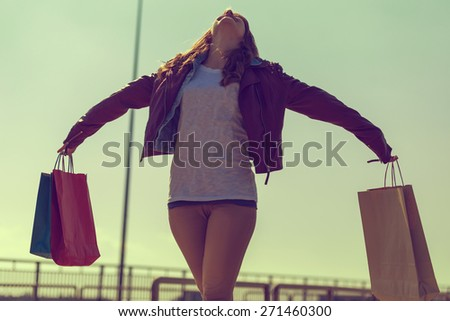 Beautiful, young brunette walking and feeling happy after successful shopping - stock photo
