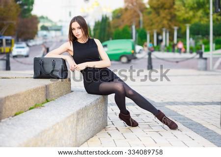 Beautiful young brunette wearing black dress posing near the road - stock photo
