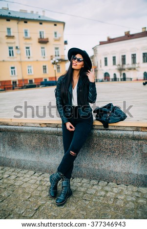 Beautiful young brunette with black hat posing and  sitting on a bench in the city streets. Spring street concept.