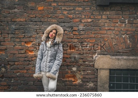Beautiful young brunette with furry hood posing in the city streets