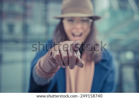 Beautiful young brunette with hat posing in the city streets - stock photo