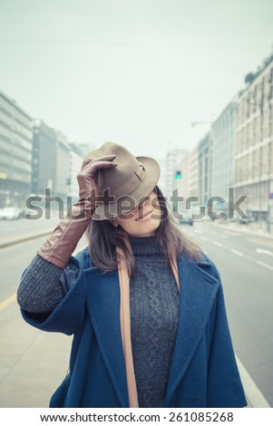Beautiful young brunette with hat posing in the city streets