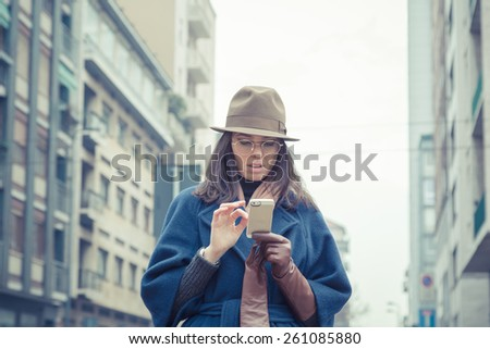 Beautiful young brunette with hat texting in the city streets - stock photo