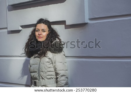 Beautiful young brunette with long curly hair posing in the city streets - stock photo