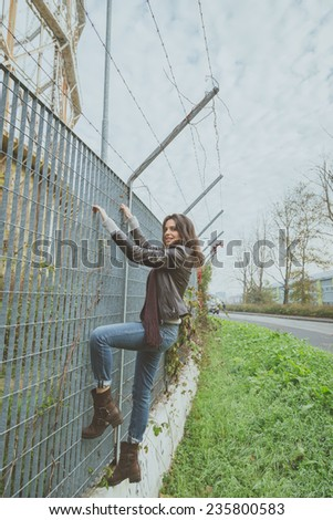Beautiful young brunette with long hair climbing over a fence