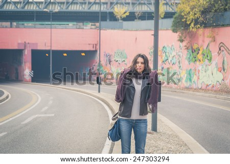 Beautiful young brunette with long hair posing in the city streets