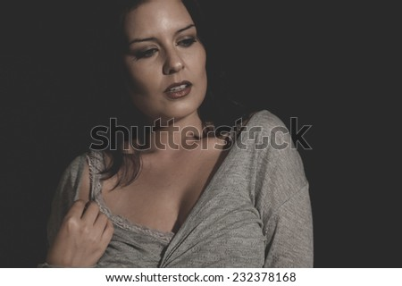 beautiful young brunette with sexy appearance, wearing a thin sweater gray - stock photo