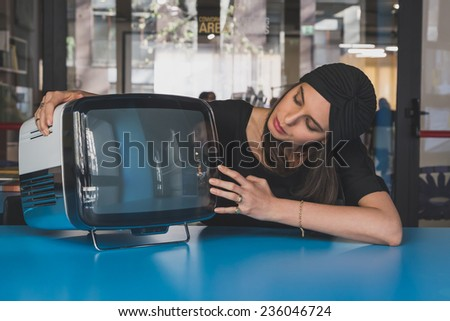Beautiful young brunette with turban posing beside a vintage tv - stock photo