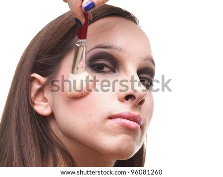 beautiful young brunette woman applying powder with a brush isolated on white