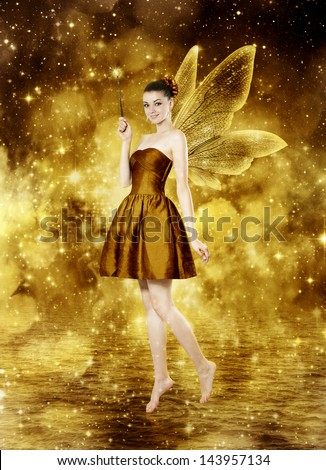 Beautiful young brunette woman as golden fairy on lake - glamour portrait - stock photo