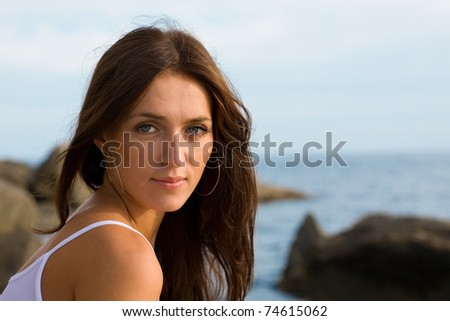 Beautiful young brunette woman at the sea. - stock photo