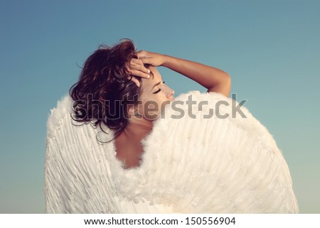 beautiful young brunette woman beauty portrait with angel wings against blue sky, outdoor shot - stock photo