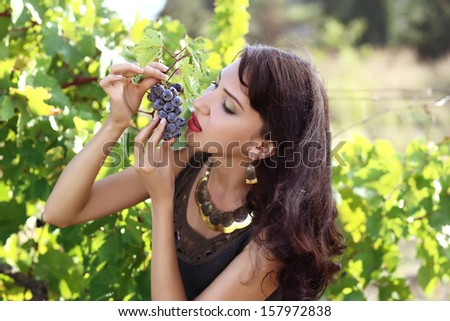 Beautiful young brunette woman bites off from grape bunches - stock photo