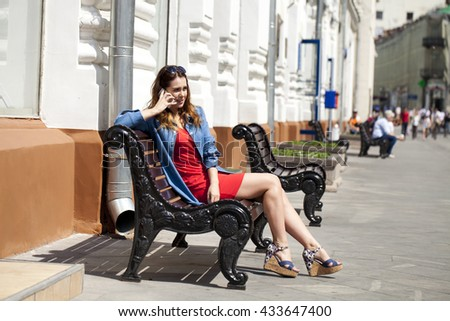 Beautiful young brunette woman calling by phone sitting on a bench outside in sunny weather - stock photo