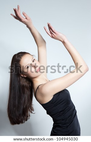 Beautiful young brunette woman dancing over gray background