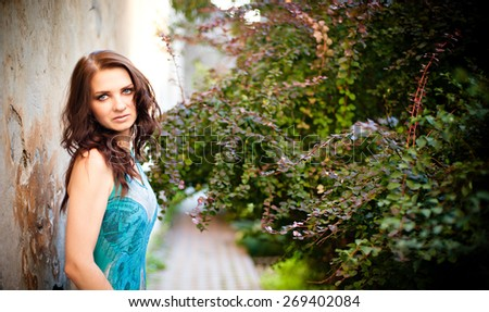 Beautiful young brunette woman dressed in a bright blue dress on the street in the garden in the old castle - stock photo