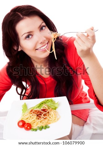 beautiful young brunette woman  eating spaghetti with vegetables and ketchup at home - stock photo