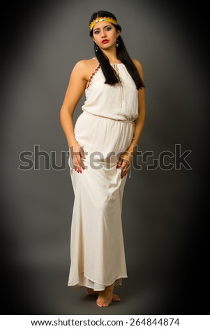 beautiful young brunette woman in a bright dress on a gray background - stock photo