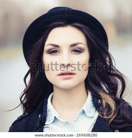 Beautiful young brunette woman in a hat outdoors - stock photo