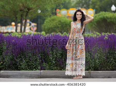 Beautiful young brunette woman in a summer dress standing on the street. The flowers on the background. Summer shot. - stock photo