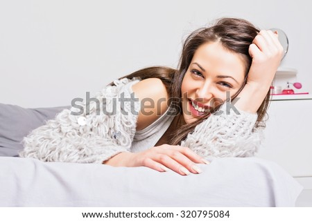 Beautiful young brunette woman in gray sweater laughing lying in bed in her modern bedroom. Cute girl relaxing at home in winter. Horizontal, medium retouch, no filter. - stock photo