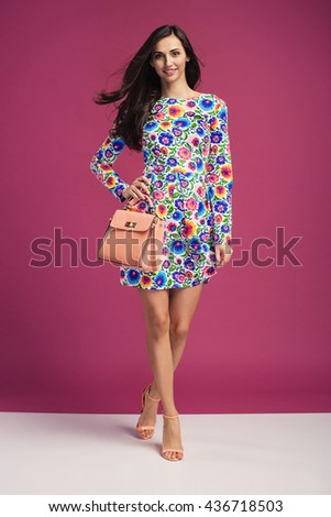 beautiful young brunette woman in nice elegant dress, posing on pink background in studio. Fashion photo