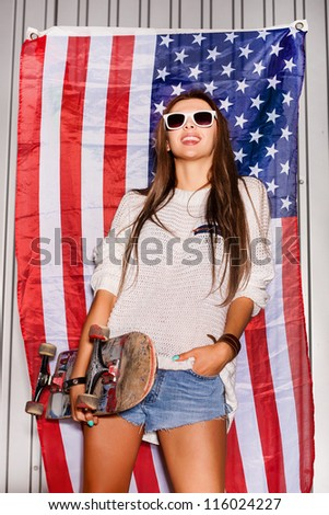 beautiful young brunette woman in style cloth and sunglasses with national usa flag in background