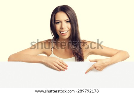 beautiful young brunette woman in tank top casual smart clothing, pointing on empty blank signboard with copyspace area for text or slogan - stock photo