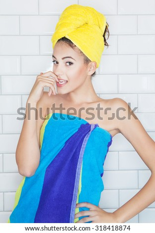 Beautiful young brunette woman in the bathroom, covered with towels, white tiles in the background.