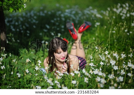 beautiful young brunette woman in the park on a warm summer day. - stock photo