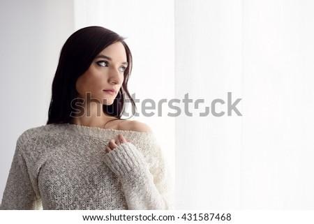 Beautiful young brunette woman in woolen sweater standing near window. - stock photo