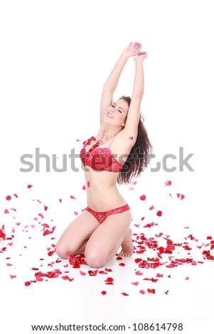 Beautiful young brunette woman kneeling and sitting on white isolated background catching the falling red rose petals while wearing sexy romantic red underwear - stock photo