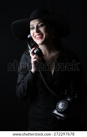 beautiful young brunette woman lady posing in a studio on a black background with old style hat  holding a telephone - stock photo