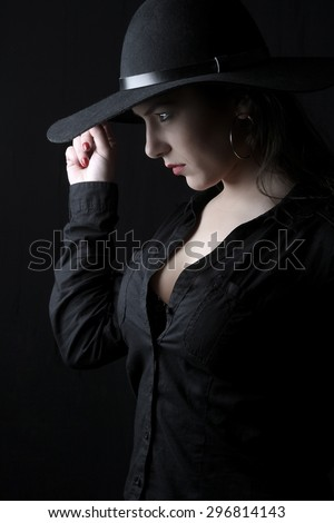 beautiful young brunette woman lady with a big breasts posing in a studio on a black background with old style hat
