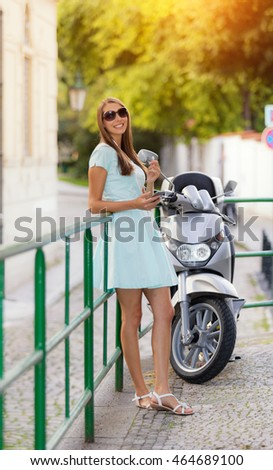 Beautiful young brunette woman listening music in headphones, holding a cup of coffee and enjoying music. Scooter motorbike on background