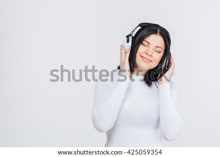 Beautiful young brunette woman listening to music, isolated on white background - stock photo