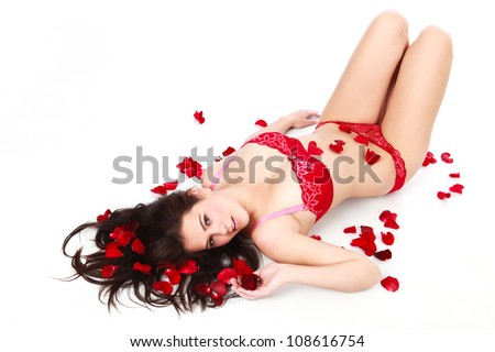 Beautiful young brunette woman lying on white isolated background among red rose petals wearing red sexy bra and pants under wear looking alluring - stock photo