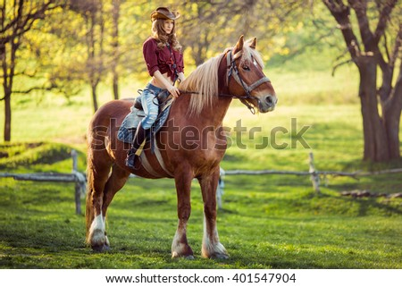 Beautiful young brunette woman on a horseback - stock photo
