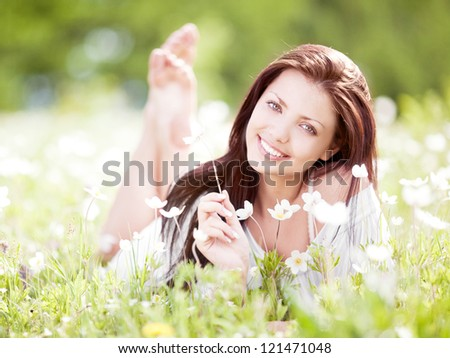 beautiful young brunette woman  on the  meadow with white flowers  on a warm summer day - stock photo