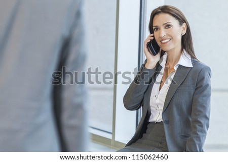 Beautiful young brunette woman or businesswoman in her thirties using cell phone and smiling at colleague or businessman