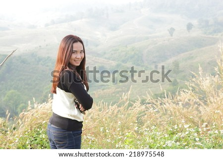 beautiful young brunette woman outdoor on the hill on a summer day. - stock photo